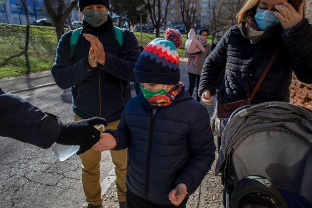 Un hombre echa gel hidroalcohólico a un niño en la cabalgata de Reyes de Aranjuez, este