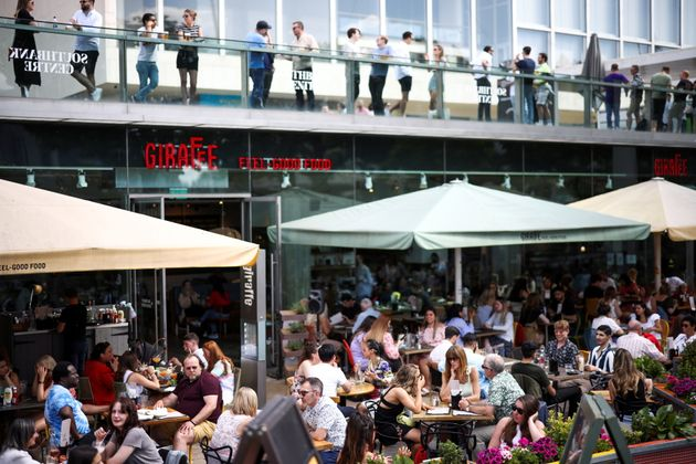 People sit at an outdoor restaurant on the South Bank during sunny weather, amid the coronavirus disease...