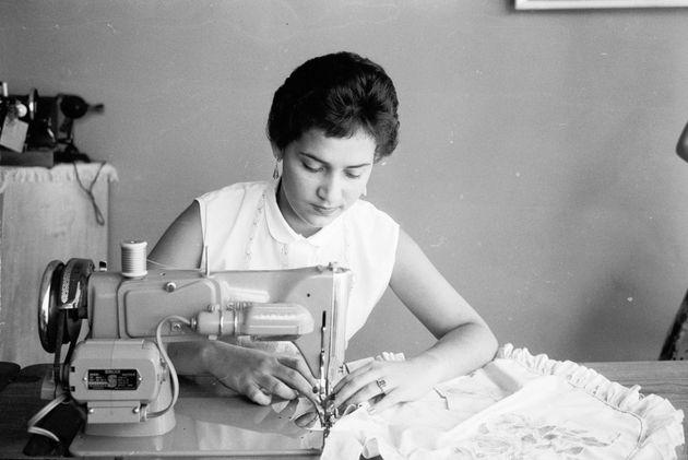 Una mujer utiliza una máquina de coser en