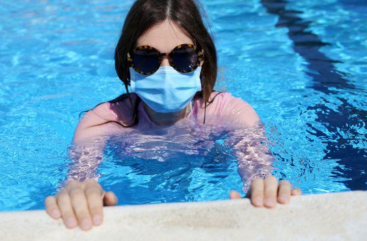 Una mujer se baña en una piscina con la mascarilla puesta.
