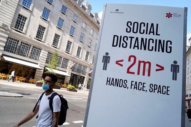 Un passant portant un masque devant un panneau demandant aux personnes de respecter les mesures de distanciation...