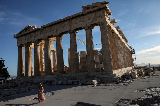 A woman wearing a protective face mask walks by the Parthenon temple atop the Acropolis hill, amid the...
