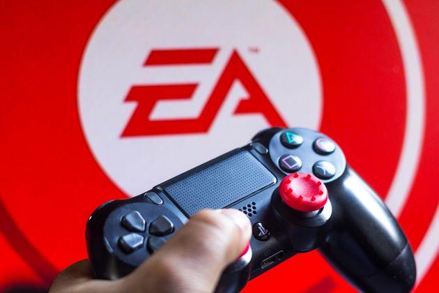 Un mando de la Playstation 4, ante el logo de la