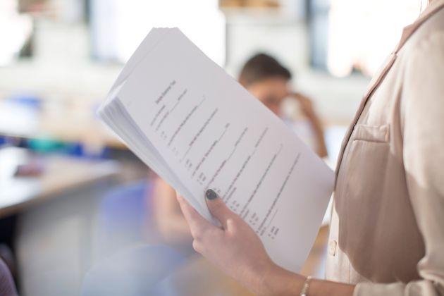 Una profesora con exámenes en la