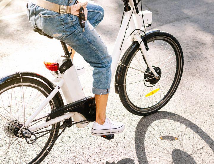 Mujer montando el bicicleta eléctrica.