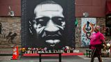 MINNEAPOLIS, MN - APRIL 06: A woman walks pass a mural of George Floyd that stands at exact location where Floyd died on Tuesday, April 6, 2021 in Minneapolis, MN. (Jason Armond / Los Angeles Times via Getty Images)