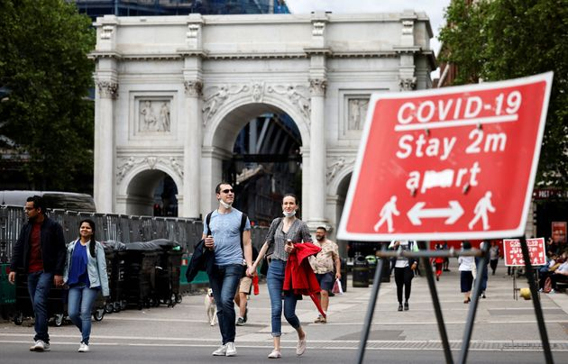 Pedestrians walk past a sign asking people to social distance, near Marble Arch in central