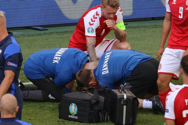 TOPSHOT - Denmark's defender Simon Kjaer (back) observes as paramedics attend to Denmark's midfielder...