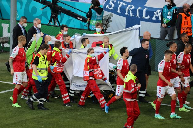 Players escort paramedics as Denmark's midfielder Christian Eriksen is evacuated from the pitch during...