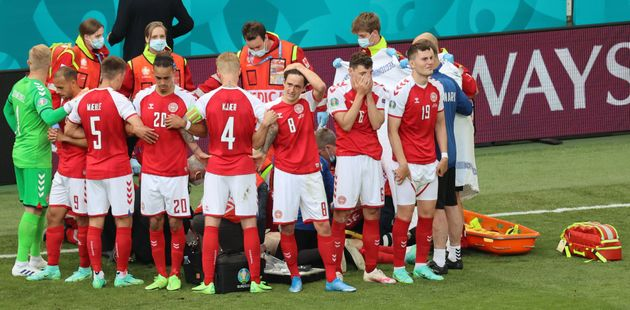 Denmark's players gather as paramedics attend to midfielder Christian Eriksen (not seen) during the UEFA...