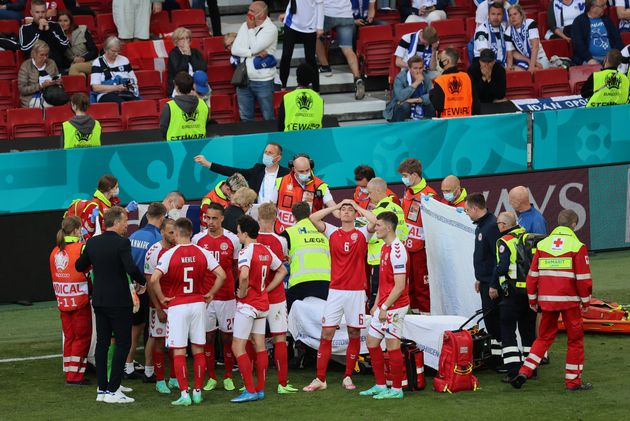 Denmark's players gather around teammate Christian Eriksen, who collapsed on the pitch during a match...