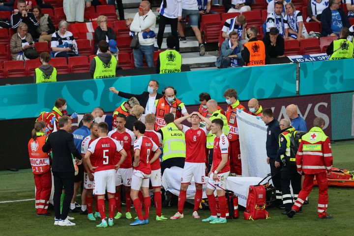 Denmark's players gather around teammate Christian Eriksen, who collapsed on the pitch during a match between Denmark and Fin
