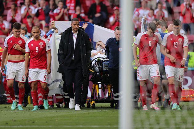 Denmark's players escort Eriksen off the