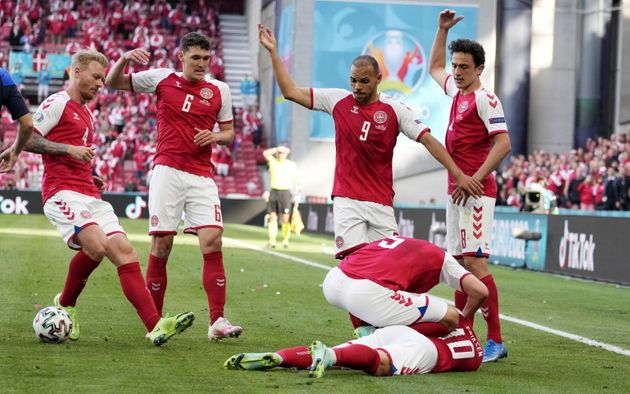 epa09265572 Players of Denmark call for medics to come onto the pitch after their teammate Christian...