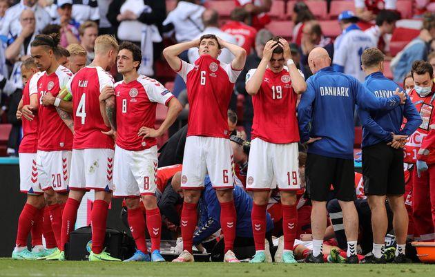 epa09266507 Players of Denmark react while their teammate Christian Eriksen receives medical treatment...