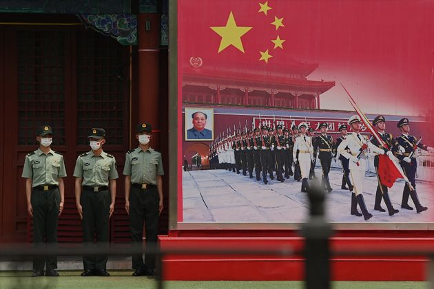 Chinese People's Liberation Army (PLA) soldiers stand guard at the entrance of the Forbidden City in...
