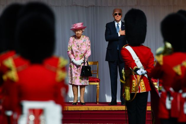 Britain's Queen Elizabeth stands and U.S. President Joe Biden stand in front of members of the Royal...
