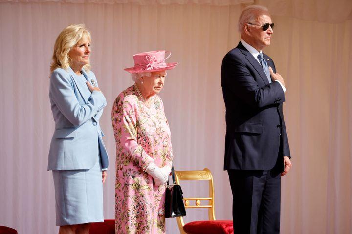 President Joe Biden and First Lady Jill Biden stand beside Britain's Queen Elizabeth II as a Guard of Honour give a Royal Sal