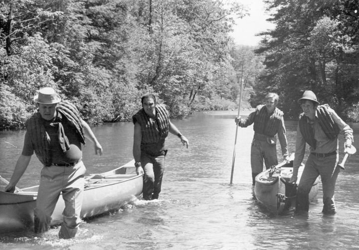 (From left to right) Actors Ned Beatty, Burt Reynolds, Jon Voight and Ronny Cox pull their canoes through the shallows of a r
