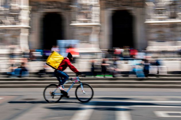 A food delivery rider cycles across Duomo square in Milan on March 25, 2019. (Photo by Miguel MEDINA...