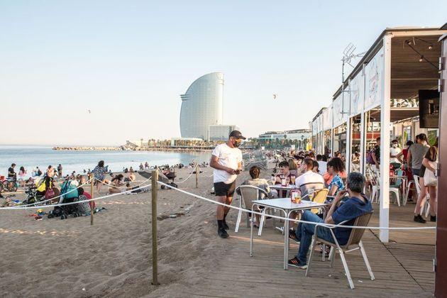 Turistas en la playa de la Barceloneta, este sábado, en
