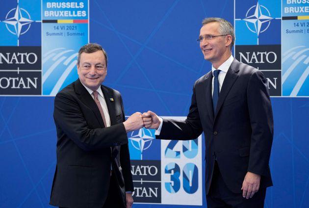 NATO Secretary General Jens Stoltenberg (R) greets Italy's Prime Minister Mario Draghi for a NATO summit...