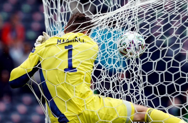 Scotland's goalkeeper, David Marshall, crashes into the back of the net after Patrik Schick's shocking goal.