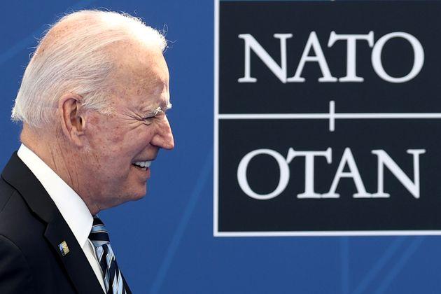 U.S. President Joe Biden arrives to pose with NATO Secretary General Jens Stoltenberg (not pictured)...