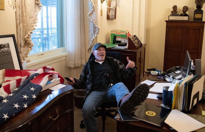 Richard Barnett shows off after breaching the Capitol and Nancy Pelosi's office.