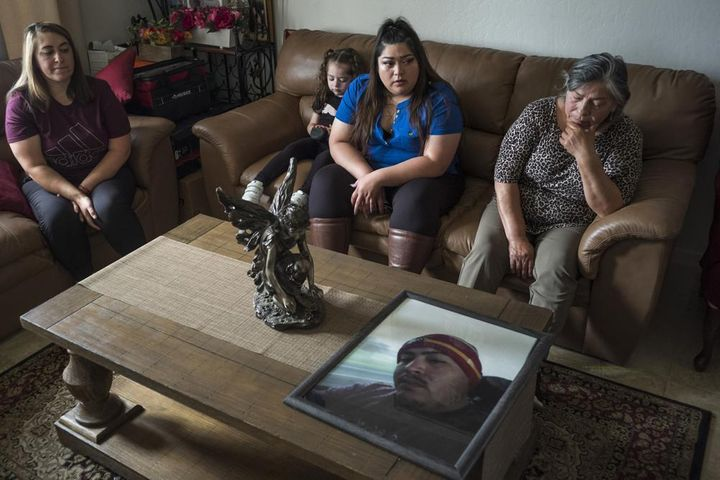 Family members of Jerry Ramos become emotional when looking at a photo of him at the family home in Watsonville, Calif., Sund