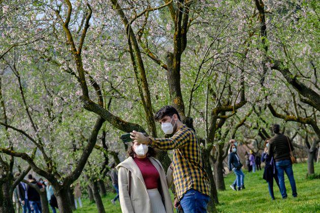Una pareja se hace un 'selfie' con las mascarilla puesta en el parque madrileño de la Quinta de los