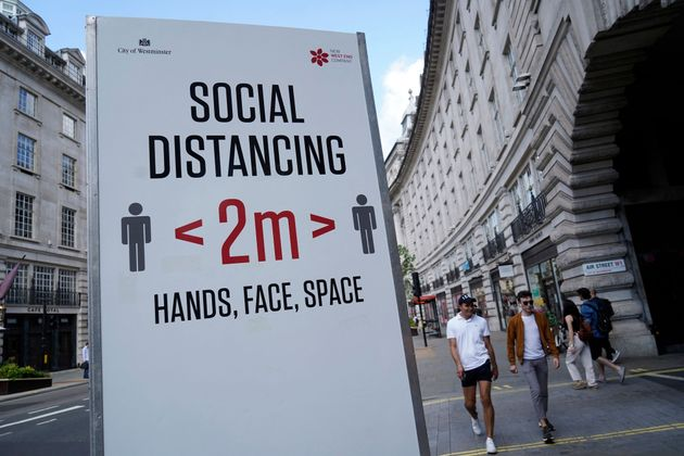Pedestrians walk past a sign asking members of the public to social distance due to Covid-19, in central...