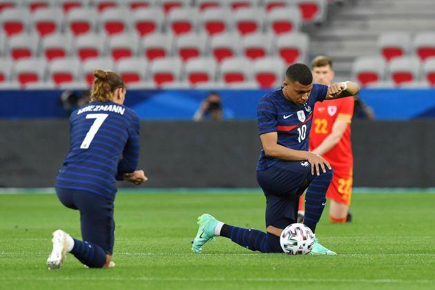 (Photo: les Bleus mettent le genou à terre contre le racisme et les discrimination lors du match...