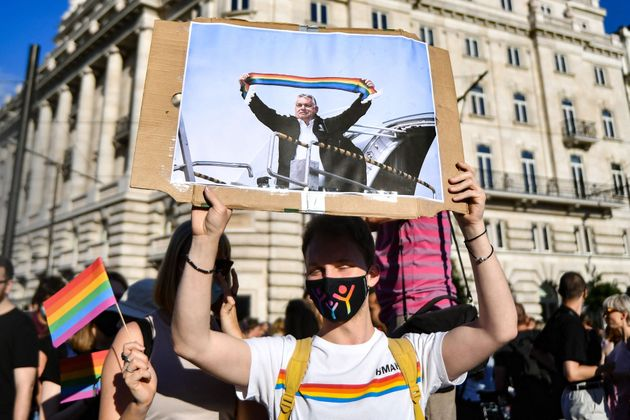 A participant holds a placard showing Hungarian Prime Minister Viktor Orban holding a scarf in rainbow...