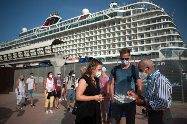 Turistas alemanes hacen cola para entrar a un bus turístico en Málaga tras desembarcar...