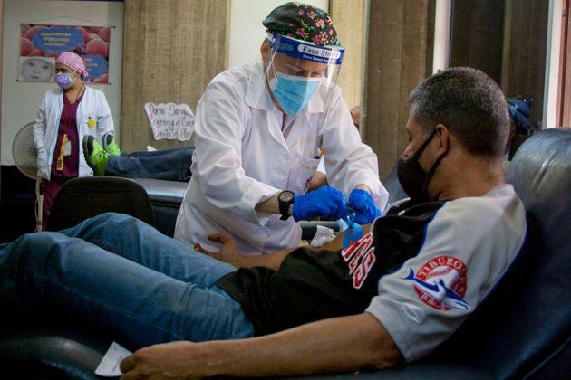 Un sanitario extrae sangre de un paciente con