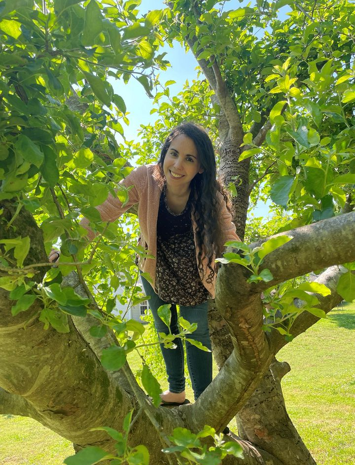 """A photo from the author's dating profile. She notes, """"I use it in part because I love climbing trees (does that count as a ho"""