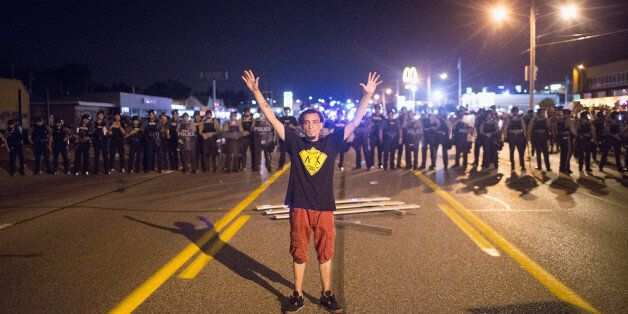FERGUSON, MO - AUGUST 10: A demonstrator, marking the one-year anniversary of the shooting of Michael Brown, confronts police during a protest along West Florrisant Street on August 10, 2015 in Ferguson, Missouri. Mare than 100 people were arrested today during protests in Ferguson and the St. Louis area. Brown was shot and killed by a Ferguson police officer on August 9, 2014. His death sparked months of sometimes violent protests in Ferguson and drew nationwide focus on police treatment of black suspects. (Photo by Scott Olson/Getty Images)