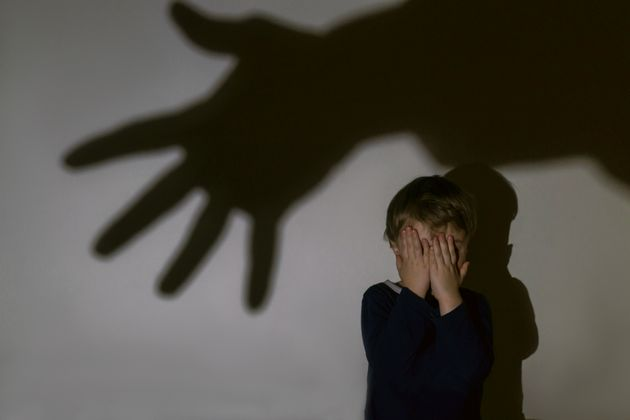 A little boy and scary shadow of hand on a light background for a fear or kidnapping concept. Boy closed...