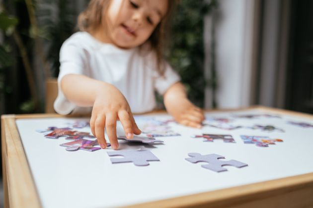 Little girl is trying to connect couple jigsaw puzzle piece. Side view of concentrated little girl playing...