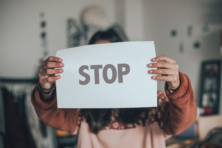 one person holding a banner with stop single word againd blue background