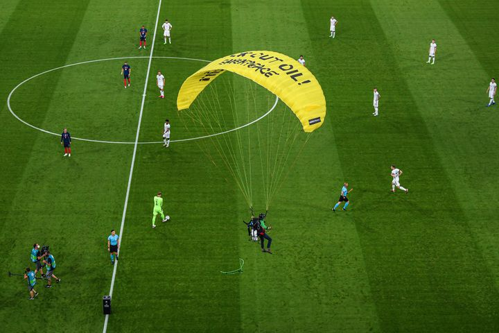 Greenpeace has apologized and Munich police are investigating after a protester parachuted into the stadium and injured two p