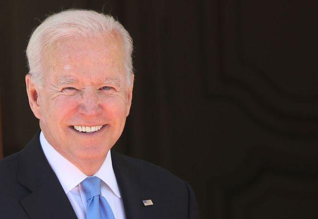 Biden sonríe a la entrada a su reunión con