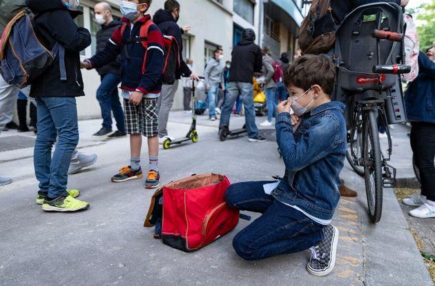 Un enfant ajuste son masque avant d'entrer à l'école, à Paris, le 26 avril
