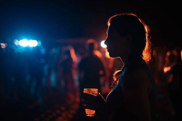 Silhouette of woman with cocktail on outdoor party.