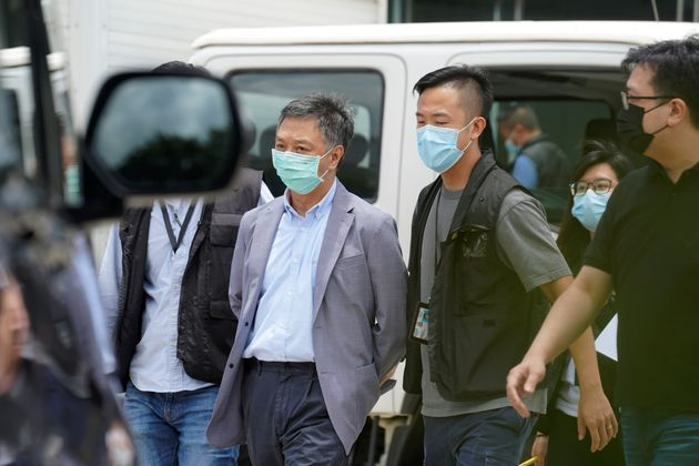 Police officers from the national security department escort Chief Operating Officer Chow Tat-kuen from...