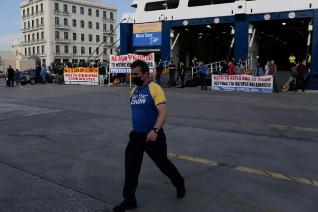 epa09275234 A crew member walks past the docked Blue Star Delos ferry during a 24-hour General strike...