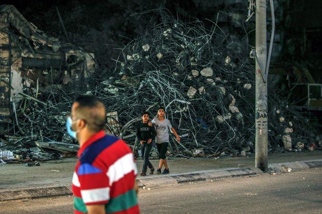Los palestinos caminan en el vecindario de Al-Remal, en Gaza, después de los ataques aéreos
