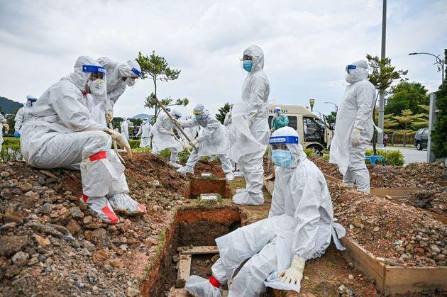 Εθελοντές με προστατευτικό εξοπλισμό βοηθούν στην ταφή των θυμάτων της πανδημίας στην Μαλαισία