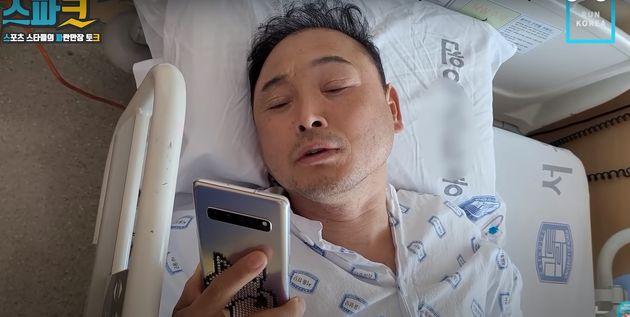 퇴원 후 촬영 예정인 프로그램을 준비하기 위해 침대 위에서 노래를 부르는 이봉주